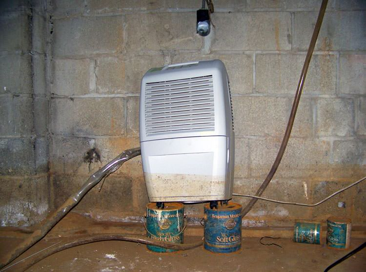 A crawl space dehumidifier up on coffee cans  with a muddy water mark  halfway up. Crawl Space Dehumidifier in Bay Area  CA   Energy Efficient