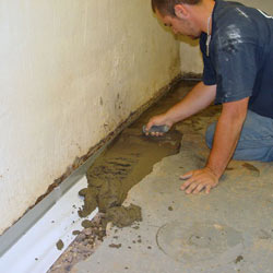 A contractor in Sacramento installing a perimeter drain tile system during a sump pump installation.